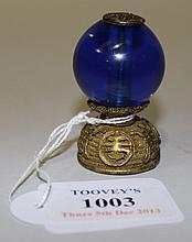 A Chinese gilt metal and blue glass hat finial,