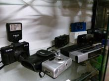 Shelf of Vintage camera equipment including Flash unit etc