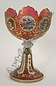 A Bohemian ruby glass tazza, with scalloped rim above circular body, overlaid with alternate portrait and floral circular panels, over flaring stem overlaid with alternate gilt scroll and flower decorated panels, the ruby glass painted allover with