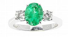 An emerald and diamond set three stone ring Ring size: M, estimated total gem weights: emerald 1.73cts, diamond 0.46cts
