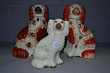 Three antique Staffordshire dogs, one in white,