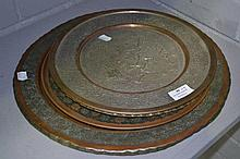 Four Persian copper wall chargers of various