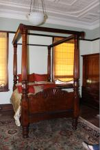 Antique Aberglasslyn House bed, important most elaborate cedar four post bed, This bed has been described by experts as an outstanding example of early Australian Furniture. It is of commanding proportions. The tapering baluster and reeded posts are decorated with bands of stylised tulip carving and joined by moulded canopy rails that are finished with inverted finials to the cornice. The shaped headboard has lightly carved ornamentation while the matching foot is decorated with