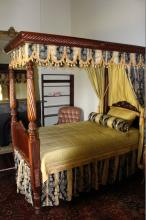 Rare early Australian cedar and iron bark four poster bed presented with full drapery, decorated in full Regency style, with circa 1820 four posts decorated with ring turning above twisted carved acanthus leaves, spiral twist body above carved pineapples, recessed knolled panels and lobed tapering legs and plain tapering head posts, the head and foot boards are carved in cedar as is the tester, the stretchers are Australian red iron bark, it is presented with full drapery, 210 cm wide x 112 cm deep x 228 cm high.  Provenance - Miss Fitzpatrick, the Westbury Inn Tasmania, Swan Murray and Hain Maitland, Keith Okey Collection Sydney (lot 170) Reference -m An image of the bed in situ at the Westbury Inn Tasmania can be seen in Early Colonial Furniture in NSW & Van Diemen's Land by Clifford Craig, Kevin Fahy & E Graeme Robertson, published Georgian House, Melbourne, 1980, page 151