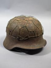 German WW2 era steel helmet with wire camouflage net, liner backing.