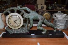 Art Deco French green patinated spelter clock of man pushing a wheel on a black marble base, has key, no pendulum, approx 38cm H x 75cm W x 15cm D