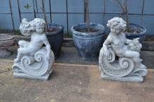 A pair of composite stone figures of putti on a C scroll, each approx 90cm H (2)