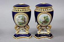 Pair of lidded Grainger and Co Worcester pierced rim and jewelled surround painted cartouches pot pourri all on tri footed bases, each approx 12cm H (one is A/F) (2)