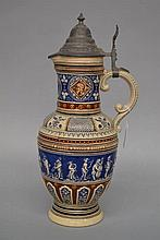 A large 19th century German pottery embossed beer jug with pewter top, appr