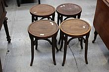 Four antique bent wood stools, each with applied labels to the sides, each