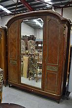 Most impressive French arched top three door armoire, fitted with cast bronze mounts, standing on tu