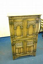 OAK CARVED DRINKS CABINET WITH ARCADED PANEL DOORS