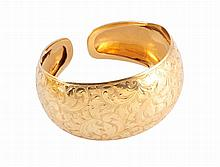 A yellow metal bangle, engraved with scrolling foliage, stamped 750 and HP. 33.8 grams