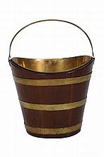 A George III mahogany and brass peat bucket, the oval tapering bucket with brass bands and enclosing a brass liner, with swing handle. 38cm wide by 29cm deep