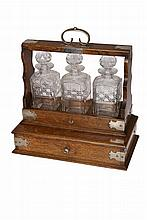 A silver plate mounted oak tantalus, early 20th Century, with lockable sliding tray, holding three cut glass decanters, over a plinth drawer, presentation plaque dated 1910, with key. 41cm high, 39.5cm wide