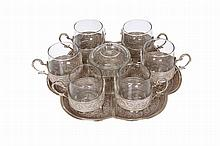 A Persian silver drinks set on tray, comprising six tea glasses and two handled sugar bowl on a lobed tray, stamped marks. Tray 31.5cm