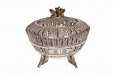 A Persian silver covered bowl, the cover and bowl cast, chased and pierced with animals and busts, enclosing a glass liner, stamped marks including 90. Silver 29oz, 15.5cm high