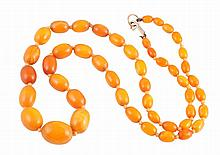 An amber coloured bead necklace, the forty seven oval graduating amber coloured beads strung knotted onto a gold lobster catch. Catch stamped 375. Total length approximately 68cm. Weight approximately 31.3gms.