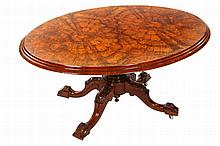 A Victorian burr walnut loo table, c.1870, the moulded and quarter veneered top tilting on a baluster stem continuing to hipped downswept legs, moving on castors. 72cm by 140cm by 102cm