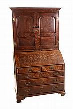 A George III oak bureau bookcase, the upper section with moulded dentil cornice over a pair of cupboard doors with ogee fielded panels and brass butterfly hinges, above a pair of slides, the base with two short over three long graduated drawers below