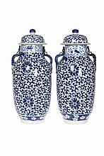 A near pair of Chinese vases and covers, late 19th Century, each ovoid body underglaze blue painted with scrolling foliage and lotus flowers, applied with ruyi handles, undercut feet and bearing four character Kangxi marks. 31cm