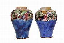 A near pair of Royal Doulton stoneware vases, of baluster form, each tubelined and hand painted with stylised fruiting foliage, impressed and incised marks. One slightly taller at 21.5cm