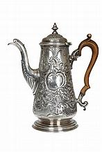 A George II silver coffee pot, Robert Innes, London 1751, the tapering body with domed cover, embossed with acanthus, C scrolls and diaper panels in the Rococo style, raised on a moulded circular foot, engraved with a crest. 28oz, 24.5cm