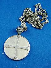 A silver pendant on chain