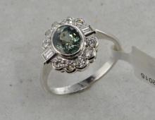 Green sapphire and diamond cluster ring, oval cut green sapphire within a brilliant and baguette cut diamond cluster, estimated total diamond weight 0.60ct, in white metal stamped and tested as 18ct, ring size Q