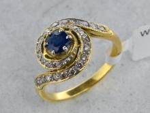 French sapphire and diamond dress ring, central round cut sapphire weighing an estimated 0.40ct, surrounded by round cut diamond set swirls, mounted in yellow metal stamped with French standard mark for 18ct, ring size M
