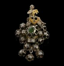 Austro-Hungarian style pendant, depicting a seated maiden holding a heart on a white metal openwork design set with an emerald and diamonds, testing as silver, 45 x 25mm
