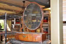 A mahogany oval dressing table mirror with open bracket feet