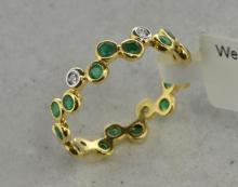 Emerald and diamond ring, three round cut emeralds rubover set, alternating with a round brilliant cut diamonds, in yellow metal stamped as 18ct, ring size L