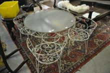 A circular garden table with glass top and four matching chairs.