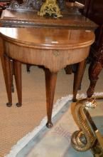A George II walnut half moon card table, the leaf opening to reveal hidden storage