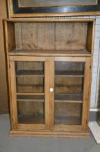 A pine cupboard with open shelves above two glazed doors