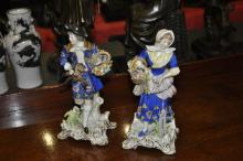 A pair of German porcelain figures of a boy and a girl, holding baskets with flowers, game and fish, on C-scroll rectangular bases, 22cm high