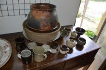 A collection of studio pottery comprising four large bowls, two small bowls, two vases and various mugs