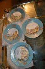 Four modern French plates with turquoise borders and centre panels painted with town scenes.
