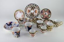 A pair of 19th century Crown Derby coffee cans with saucers; a Royal Crown Derby trio with loving cup; town further coffee cans and saucers and a Royal Crown Derby coffee can with teaplate