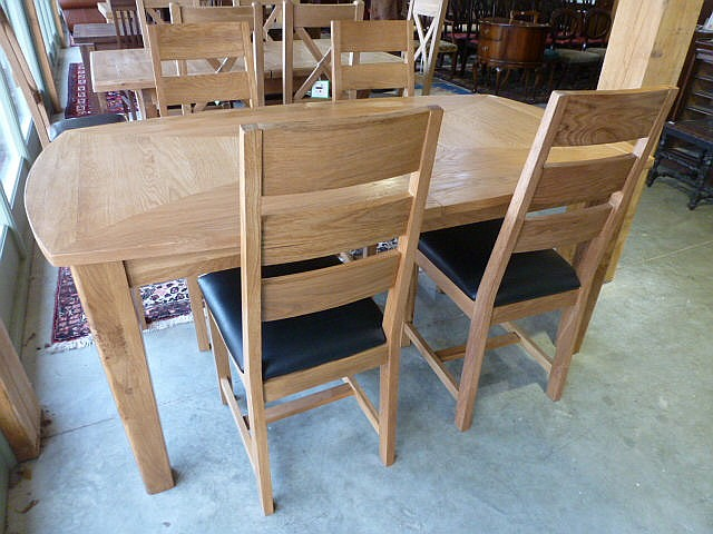 An oak extending dining table with one removable