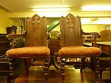 A pair of gothic revival oak open armchairs with triple lancet shaped moulded pa