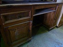 A Mexican pine kneehole pedestal desk partially enclosed by a pair of cupboards
