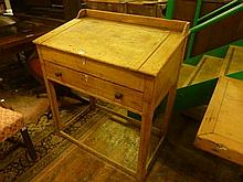 A 19th century stripped pine clerk's desk with shallow raised gallery over a hin