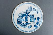 A BLUE AND WHITE PORCELAIN PLATE DEPICTING A HUMOROUS SCENE IN AN ANTIQUARIAN SHOP