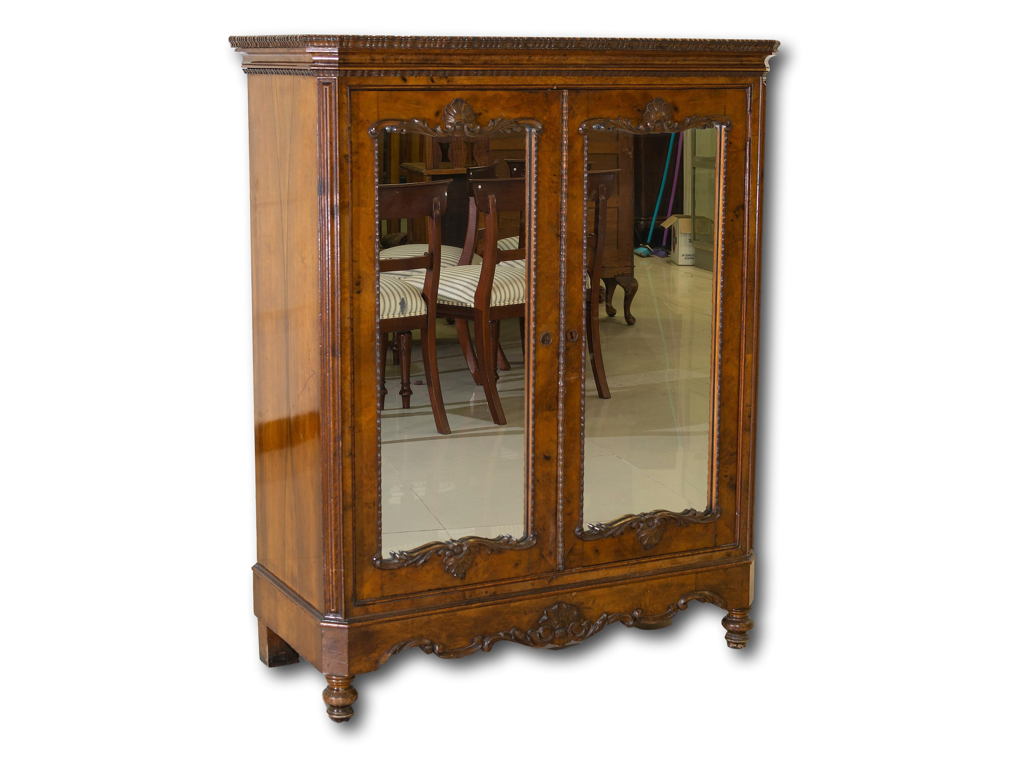 A Victorian Carved Walnut Pier Cabinet with Mirrored Doors, 133 x 107 x 49