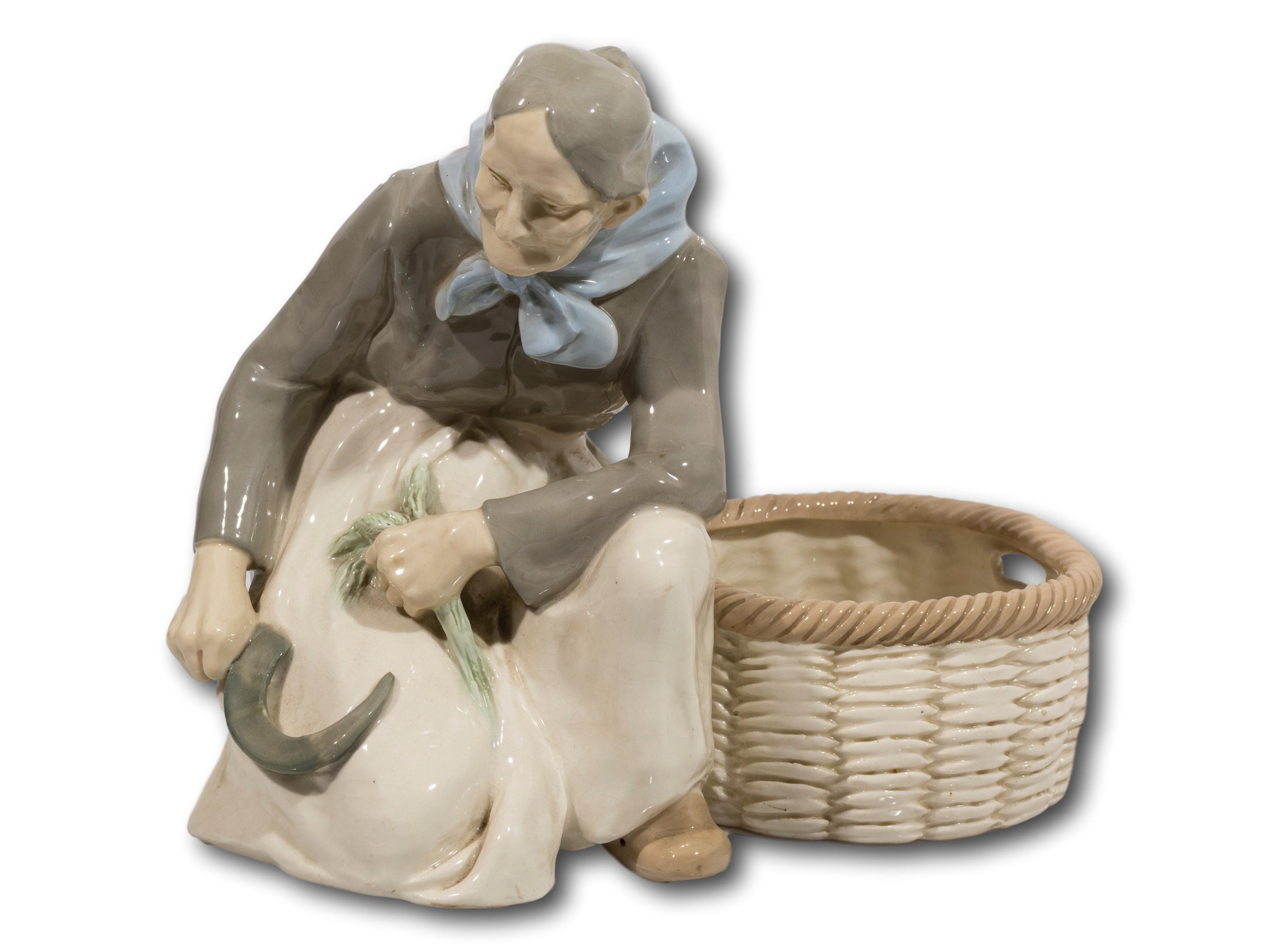 A Porcelain Figurine of a Wheat Cutter & Basket, Stamped Amphora Austria, 23cm