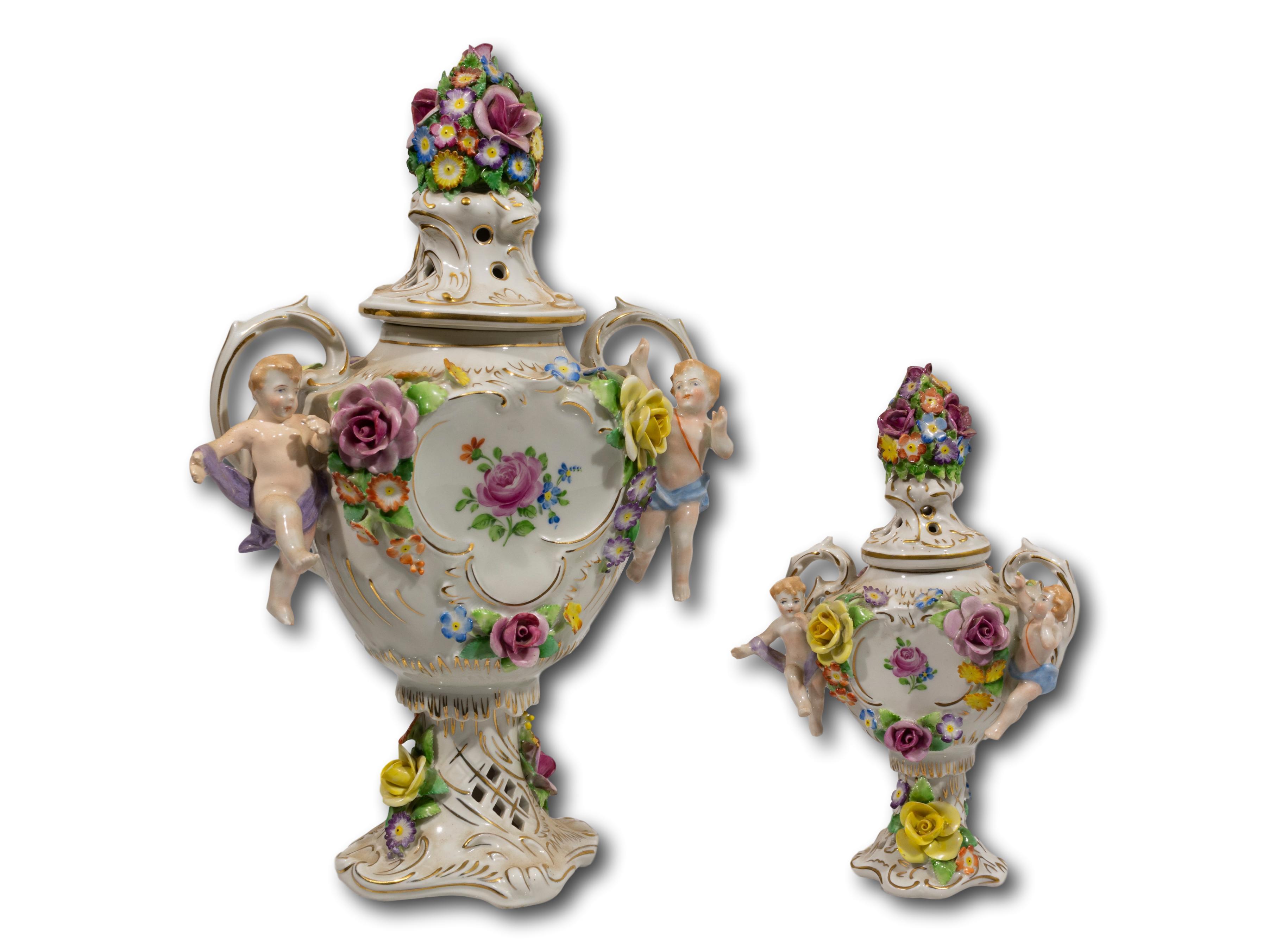 A Pair of Sitzendorf Porcelain Cherub Covered Urns, 32cm & 20cm