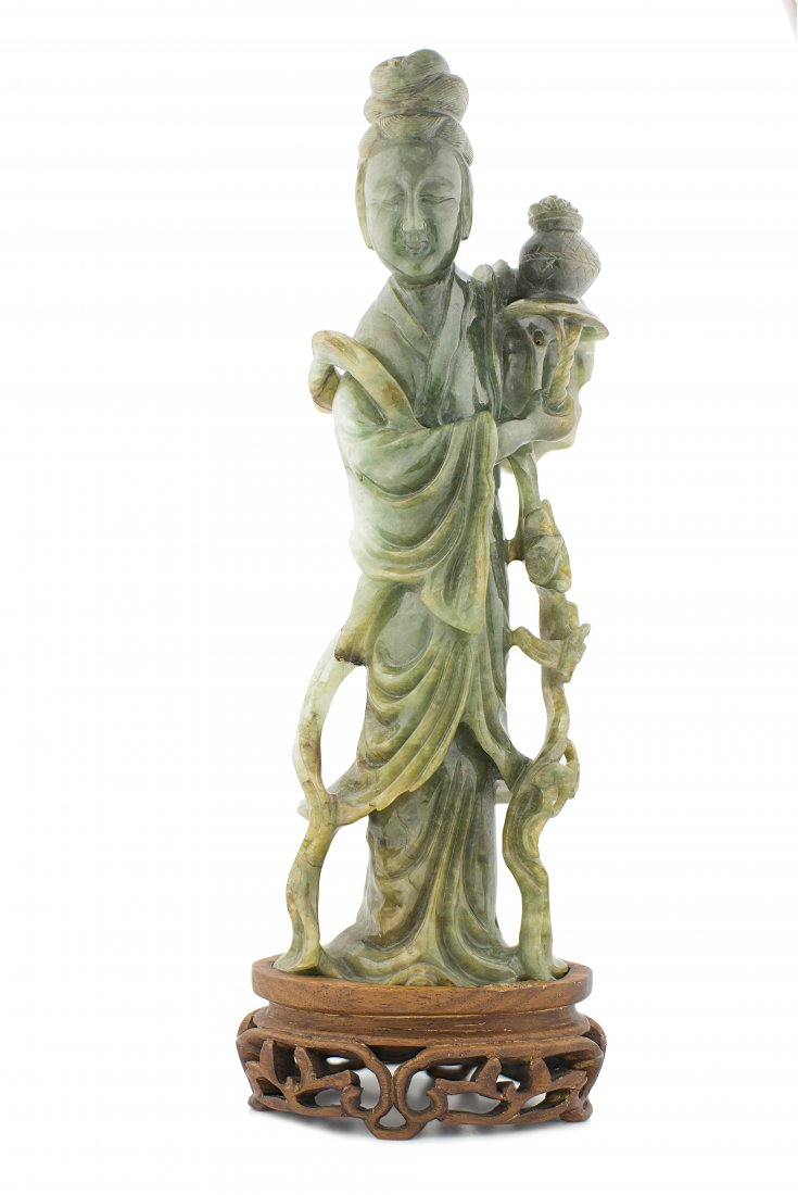 A FINE TRANSLUCENT GREEN JADE FIGURE OF GUANYIN