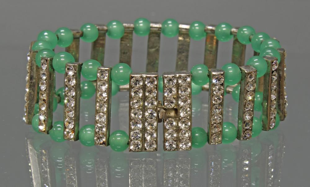 Art Deco-Armband, um 1920/30, Weißmetall, 21 Stege mit weißen Pastesteinen und 40 grünen Glaskügelchen, 17.5 cm lang.